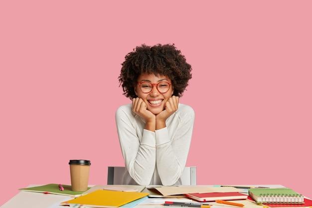 Uradowana etniczna dziwka nosi okulary, ma zębaty uśmiech, przygotowuje się do zbliżającego się egzaminu