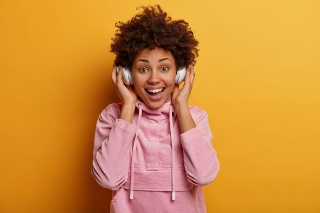 Uradowana etniczna nastolatka w pozytywnym nastroju słucha muzyki przez nowoczesne słuchawki, wygląda radośnie, cieszy się dobrym czystym dźwiękiem, spędza wolny czas słuchając ulubionych piosenek, ubrana niedbale