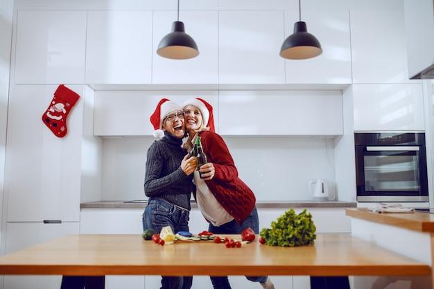 Uradowana kaukaska starsza kobieta i jej córka opiekania piwem w kuchni w wigilię bożego narodzenia. oboje mają na głowie czapki mikołaja. na kuchennym blacie leżą warzywa.