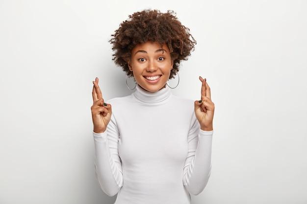 Uradowana kobieta o kręconych włosach trzyma kciuki, życzy sobie szczęścia w przyszłości, nosi swobodny biały sweter z poloneck, uśmiecha się delikatnie, ma nadzieję na cuda