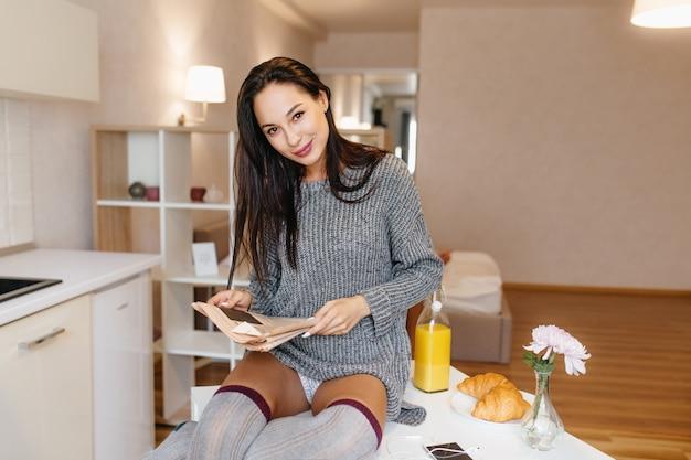 Uradowana kobieta pozuje figlarnie w swoim pokoju z gazetą, pijąc sok pomarańczowy