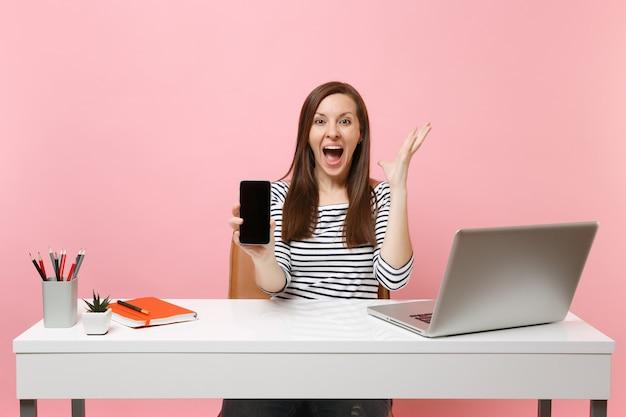 Uradowana kobieta rozkładając ręce trzymając telefon komórkowy z pustym pustym ekranem pracy przy białym biurku z nowoczesnym laptopem pc na białym tle na pastelowym różowym tle. osiągnięcie kariery biznesowej. skopiuj miejsce.