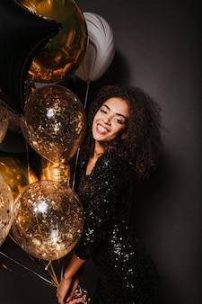 Uradowana kobieta trzyma złote balony z uroczym uśmiechem