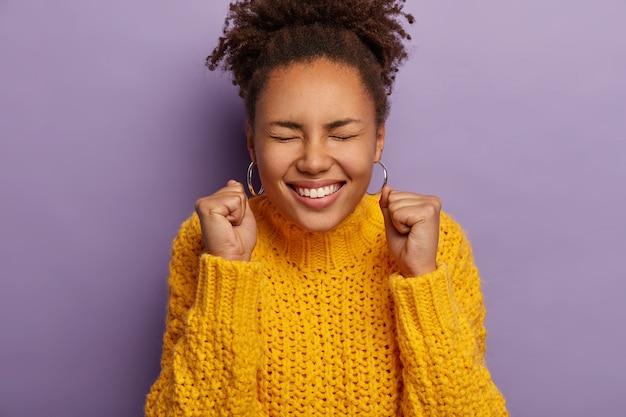 Uradowana kobieta z kręconymi włosami unosi zaciśnięte pięści, jest podekscytowana, świętuje sukces, nosi ciepły żółty sweter z dzianiny