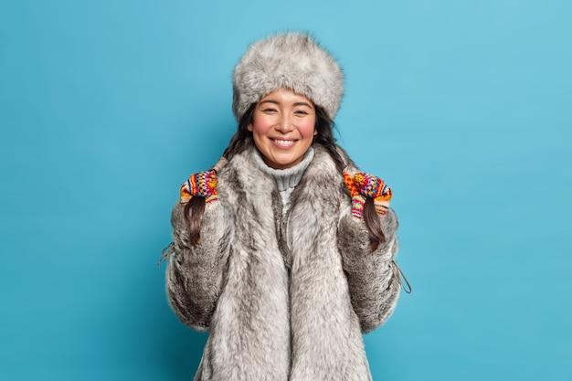 Uradowana kobieta z północy trzyma warkocze i szeroko się uśmiecha, nosi szary futrzany kapelusz i płaszcz w pozach w domu na niebieskiej ścianie