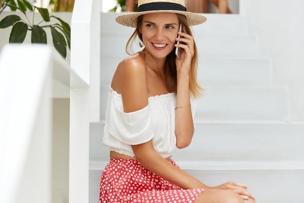Uradowana kobieta z zaciekawieniem patrzy na bok, lubi komunikować się za pomocą smartfona, siada na schodach w hotelu, opowiada o swoich udanych wakacjach w egzotycznym kraju. koncepcja ludzi, technologii i piękna