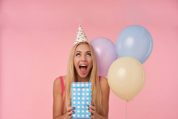 Uradowana młoda, długowłosa blondynka jest podekscytowana i zaskoczona prezentami urodzinowymi, radosnymi chwilami w życiu podczas przyjęcia urodzinowego, pozuje na różowym tle