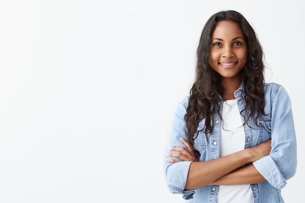 Uradowana młoda, dobrze wyglądająca afroamerykańska kobieta o czystej ciemnej skórze i czarnych długich włosach pozuje w pomieszczeniu ze skrzyżowanymi rękami, uśmiecha się szeroko z białymi zębami, śmieje się z dobrego żartu, ma na sobie dżinsową koszulę