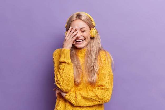 Uradowana młoda europejka o blond włosach, głośno się śmieje, sprawia, że dłoń słucha muzyki przez słuchawki bezprzewodowe, nosi swobodny żółty sweter