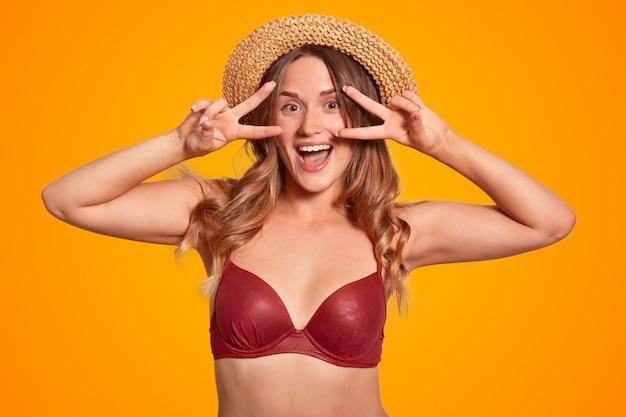 Uradowana młoda europejska suczka z pozytywnym wyrazem twarzy robi znak pokoju, ma długie włosy, nosi stylowy słomkowy kapelusz i czerwone bikini, latem bawi się na plaży, izolowana na pomarańczowo