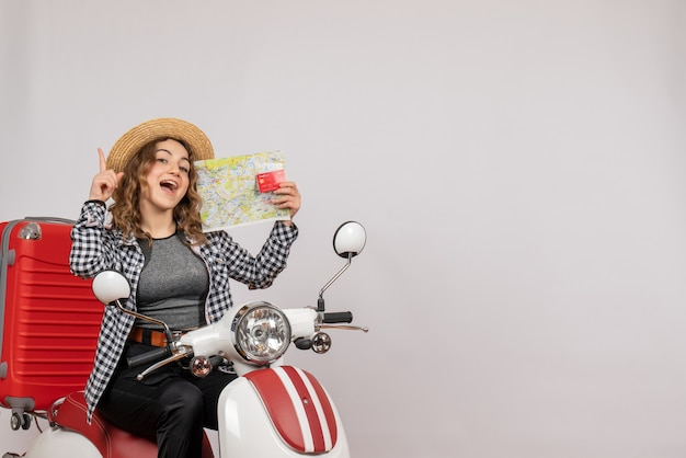 Uradowana młoda kobieta na motorowerze trzymająca kartę i mapę na szaro