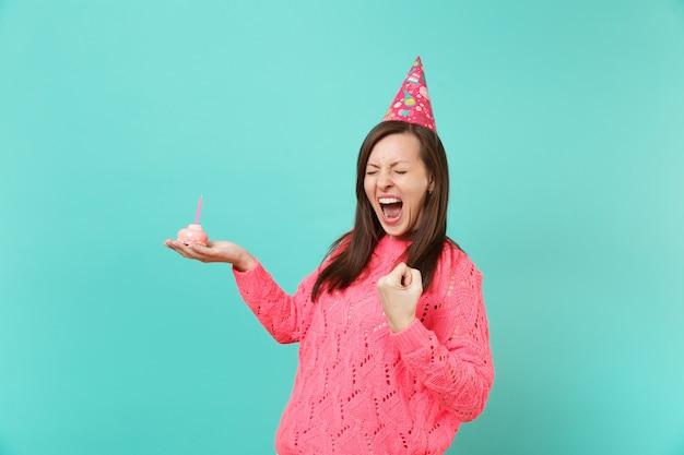 Uradowana młoda kobieta w kapeluszu z dzianiny różowy sweter urodzinowy krzyczy zaciskając pięść jak zwycięzca trzymaj w ręku ciasto ze świecą na białym tle na niebieskim tle. koncepcja życia ludzi. makieta miejsca na kopię.