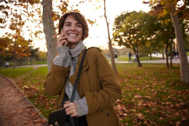 Uradowana młoda, krótkowłosa brunetka uśmiecha się radośnie podczas rozmowy telefonicznej, spotyka się z przyjacielem w weekend w miejskim ogrodzie, ubrana w stylowe ciepłe ubrania