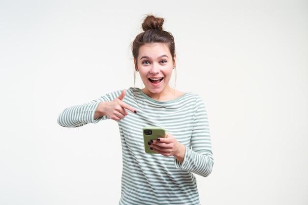 Uradowana młoda ładna brązowowłosa kobieta z przypadkową fryzurą, patrząc podekscytowana z przodu, pokazując na swoim smartfonie, stojąc nad białą ścianą