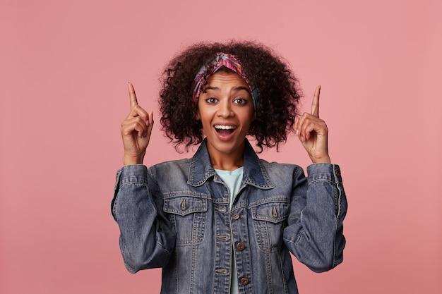 Uradowana młoda, ładna ciemnoskóra brunetka dama w kolorowym pałąku, ubrana w miętowy t-shirt i dżinsowy płaszcz, wskazująca w górę palcami wskazującymi i uśmiechnięta radośnie
