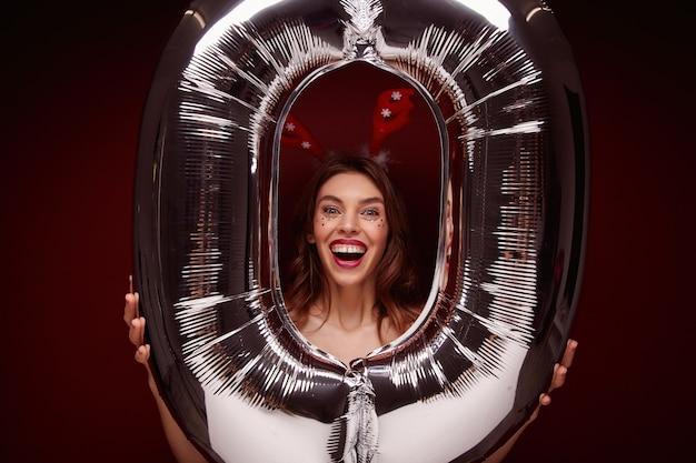 Uradowana młoda ładna dama z brązowymi falującymi włosami trzymająca w dłoniach ogromny balon i wyglądająca wesoło, śmiejąca się z szeroko otwartymi ustami
