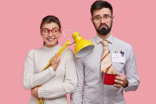 Uradowana młoda uczennica w białym swetrze, nosi okulary, trzyma żółtą lampkę na biurku, stoi blisko kolegi z klasy