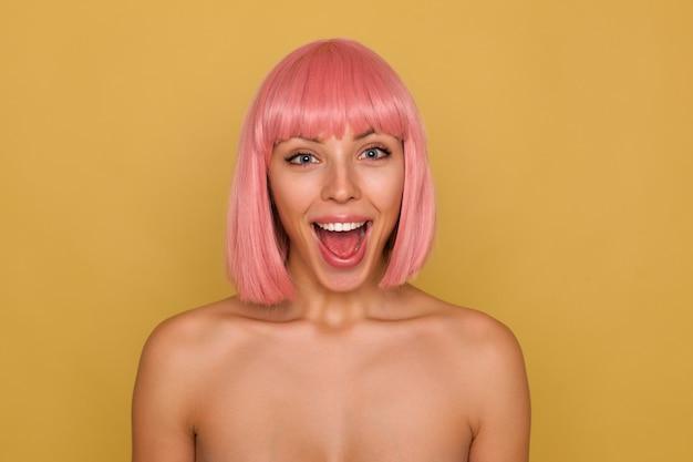Uradowana młoda, urocza różowowłosa kobieta z fryzurą boba, patrząc radośnie na aparat z szeroko otwartymi ustami, będąc w duchu, stojąc nad musztardową ścianą