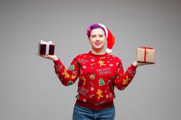 Uradowana pani rozkładająca ramiona na boki i trzymająca prezent na każdej dłoni. koncepcja nowego roku