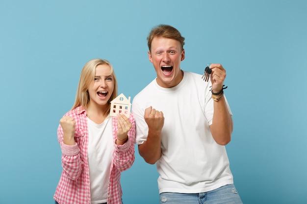 Uradowana para dwóch przyjaciół, facet i kobieta w białych różowych koszulkach pozują