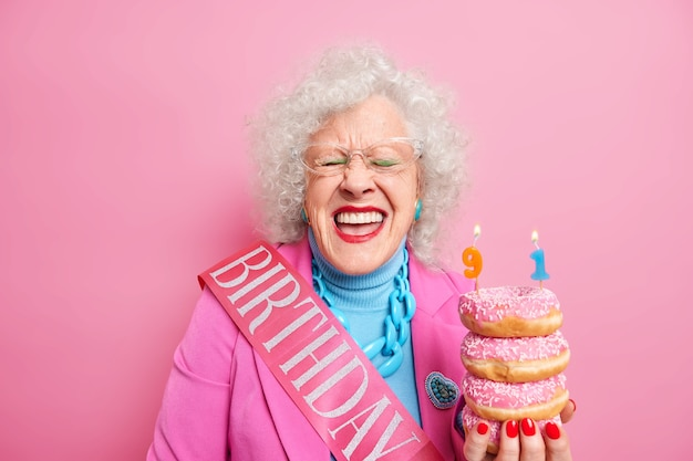 Uradowana pomarszczona emerytka z jasnym makijażem uśmiecha się szeroko trzyma stos glazurowanych pączków świętuje 91 urodziny zamierza zdmuchnąć świeczki nosi różowy kostium przezroczyste okulary pozuje w pomieszczeniu
