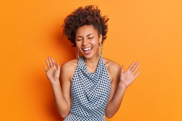Uradowana, pozytywna młoda afroamerykanka ma modną fryzurę, ubrana w bluzkę w kropki, uśmiecha się szeroko unosi dłonie, dobrze się bawi na przyjęciu, zamyka oczy, pozuje na tle jaskrawo pomarańczowej ściany studia