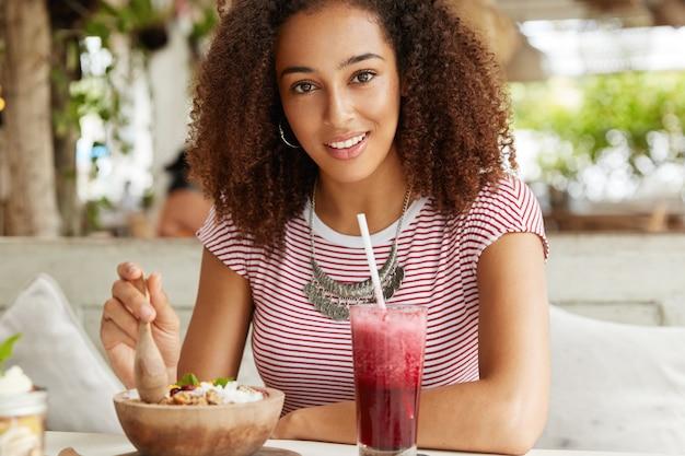Uradowana, pozytywna młoda studentka cieszy się wakacjami za granicą, spędza wolny czas w kawiarni, je sałatkę i czerwone smoothie, ubrana swobodnie, lubi przebywać w dobrym towarzystwie. koncepcja ludzi i stylu życia