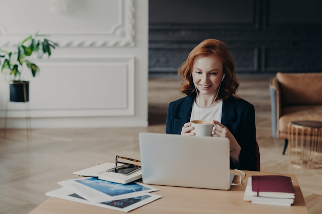 Uradowana rudowłosa kobieta ma pracę na odległość, komunikuje się na czacie wideo z kolegami