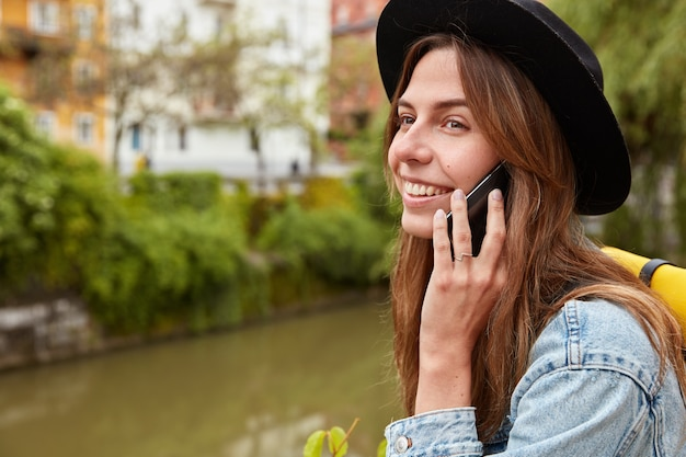 Uradowana, urocza turystka stoi na tle małej rzeki w mieście, rozmawia przez telefon komórkowy, korzysta z połączenia roamingowego