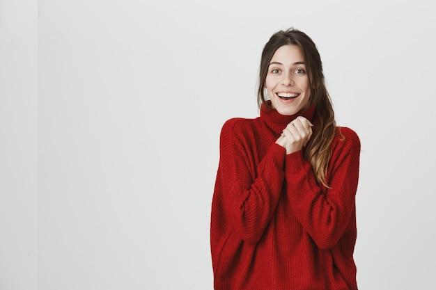 Uradowana uśmiechnięta kobieta raduje się, klaszcze w dłonie z ulgą