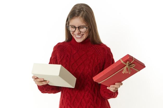 Uradowana, zadowolona młoda urodzinowa dziewczyna pozuje przy białej ścianie z otwartym fantazyjnym pudełkiem, patrząc do środka z podekscytowaniem i przyjemnością