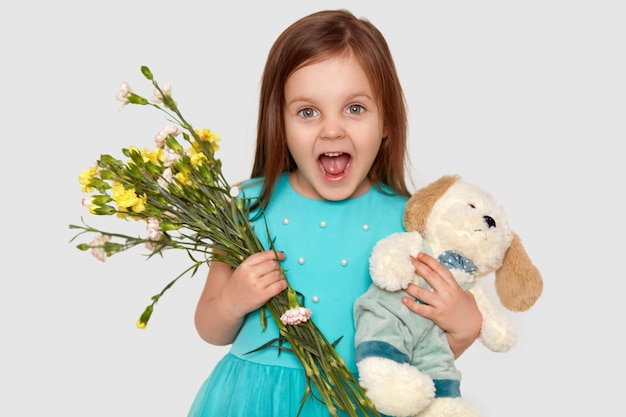Uradowane małe dziecko o niebieskich oczach trzyma swoją ulubioną zabawkę i kwiaty, chętnie przyjmuje prezent na urodziny, szeroko otwiera usta, ubrana w świąteczną sukienkę, na białym tle