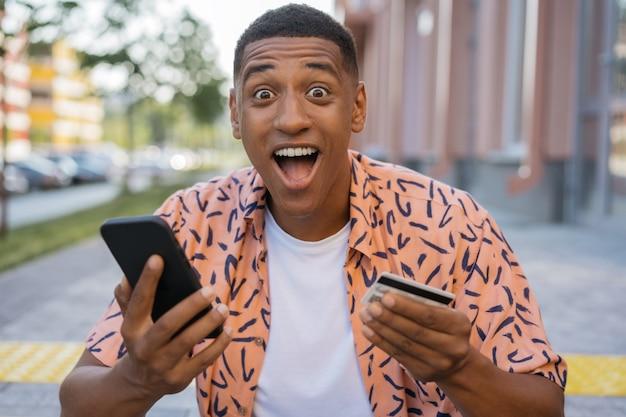 Uradowany afroamerykanin trzymający kartę kredytową robiący zakupy online z wyprzedażami w czarny piątek