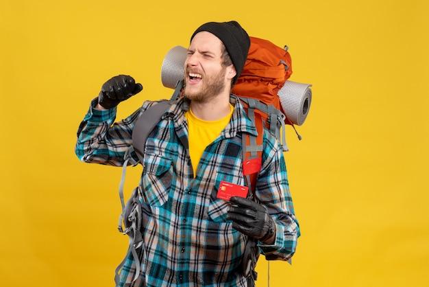 Uradowany młody człowiek z backpackerem posiadającym kartę rabatową