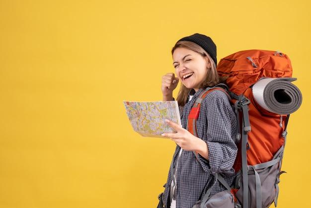 Uradowany młody podróżnik z plecakiem trzymającym mapę