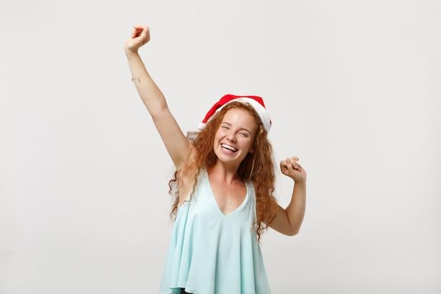 Uradowany młody rudowłosy santa dziewczyna w lekkich ubraniach, świąteczny kapelusz na białym tle na białym tle w studio. szczęśliwego nowego roku 2020 celebracja wakacje koncepcja. makieta miejsca na kopię. robi gest zwycięzcy.