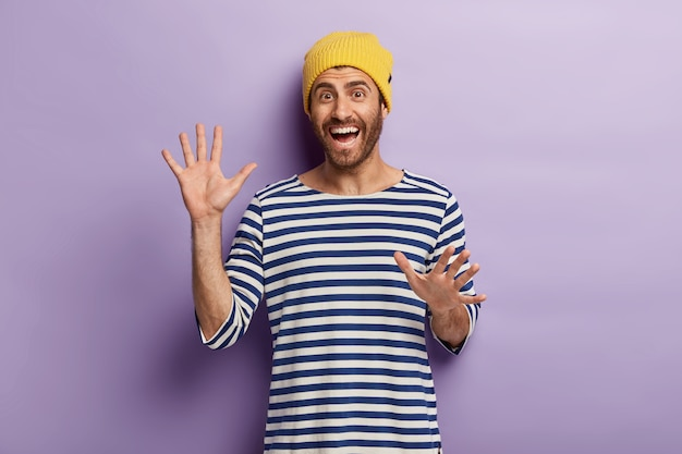 Uradowany, nieogolony tysiącletni facet aktywnie gestykuluje, pokazuje dłonie, jest w dobrym nastroju, nosi żółtą czapkę i sweter w paski