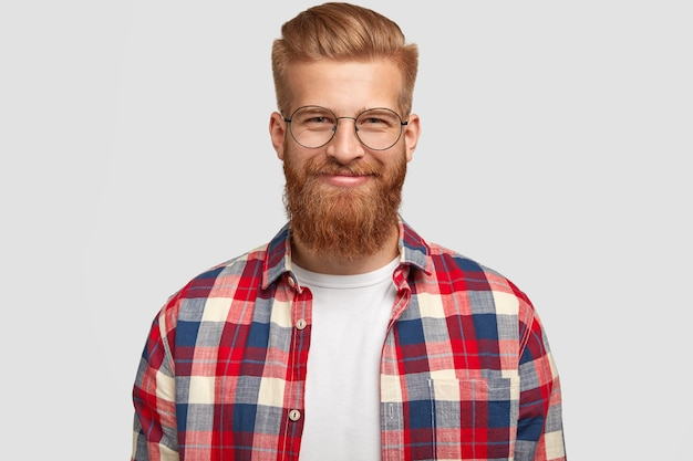 Uradowany rudy mężczyzna z zadowolonym wyrazem twarzy, nosi okulary i modną kraciastą koszulę, raduje się pomyślnie wykonanym projektem, pozuje samotnie na białej ścianie. ludzie, emocje, styl życia