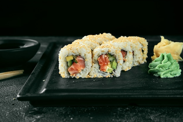 Uramaki sushi california roll w sezamie z łososiem, awokado i ogórkiem. klasyczna kuchnia japońska. dostawa jedzenia.