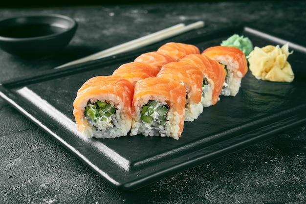 Uramaki sushi philadelphia z łososiem, ogórkiem i awokado. klasyczna kuchnia japońska. dostawa jedzenia.