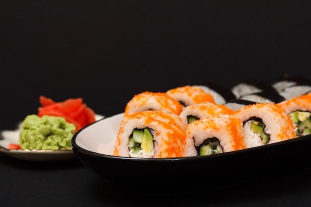 Uramaki w kalifornii. roladki sushi z nori, ryżem, kawałkami awokado, ogórkiem, ozdobione ikrą latającej ryby na talerzu ceramicznym. talerz z czerwonym marynowanym imbirem i wasabi. czarne tło.