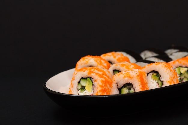 Uramaki w kalifornii. roladki sushi z nori, ryżem, kawałkami awokado, ogórkiem, ozdobione ikrą latającej ryby na talerzu ceramicznym w czarnym tle.