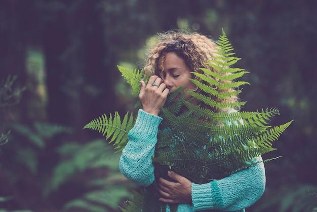 Uratuj planetę ziemi i świętuj dzień ziemi z dorosłą kobietą, która przytula się i trzyma zielony liść w lesie, ciesząc się przyrodą