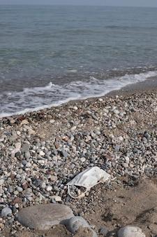 Uratuj plantę. natura. wybrzeże ze śmieciami. kamienna plaża z maską medyczną