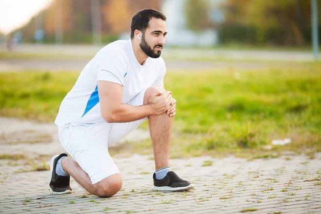 Uraz nóg. mężczyzna sportowiec cierpi na ból nogi podczas ćwiczeń na świeżym powietrzu