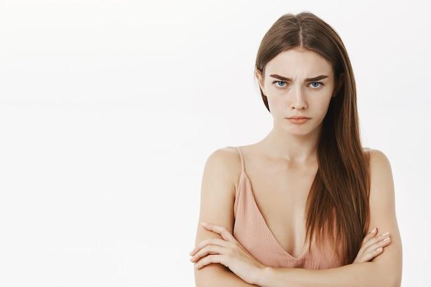 Urażona ponura i zdenerwowana śliczna młoda kobieta krzyżuje ramiona na klatce piersiowej w obronnej pozie, stoi niezadowolona i intensywna
