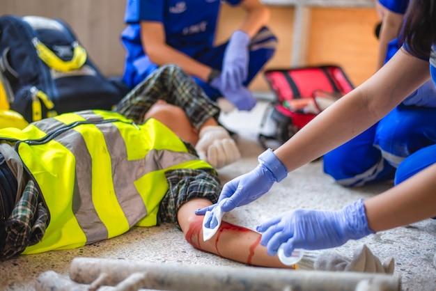 Urazy fizyczne przy pracy robotnika budowlanego. ekipy ratownictwa medycznego udzielają pierwszej pomocy pracownikowi budowlanemu, który uległ wypadkowi na budowie.