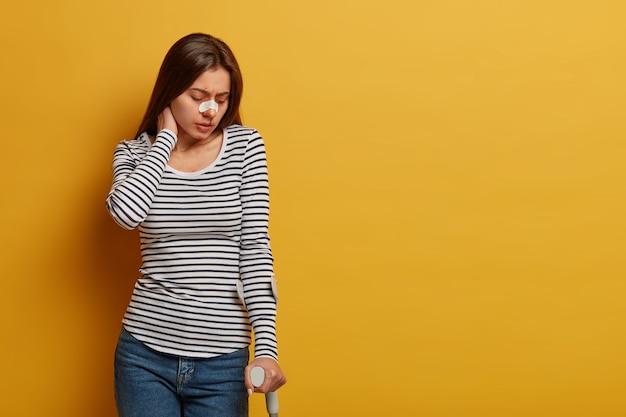 Urazy nóg i ograniczenie ruchu człowieka. niezadowolona kobieta dotyka szyi, odczuwa ból, doznała kontuzji podczas niebezpiecznej podróży, ma złamany nos, pozuje na żółtej ścianie, odkładając puste miejsce.
