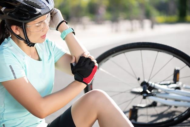 Urazy roweru. kobieta rowerzysta spadł z roweru drogowego podczas jazdy na rowerze.
