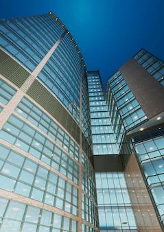 Urban geometry, patrząc na szklany budynek. nowoczesna architektura, szkło i stal. abstrakcyjny projekt architektoniczny. inspirujący, artystyczny wizerunek. wzornictwo przemysłowe. nowoczesne budownictwo. renderowania 3d.